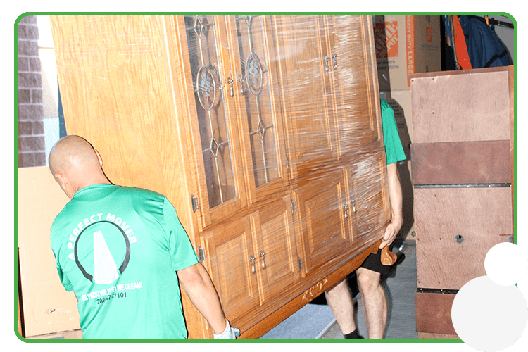 This image shows 2 professional movers carrying a large piece of wrapped furniture